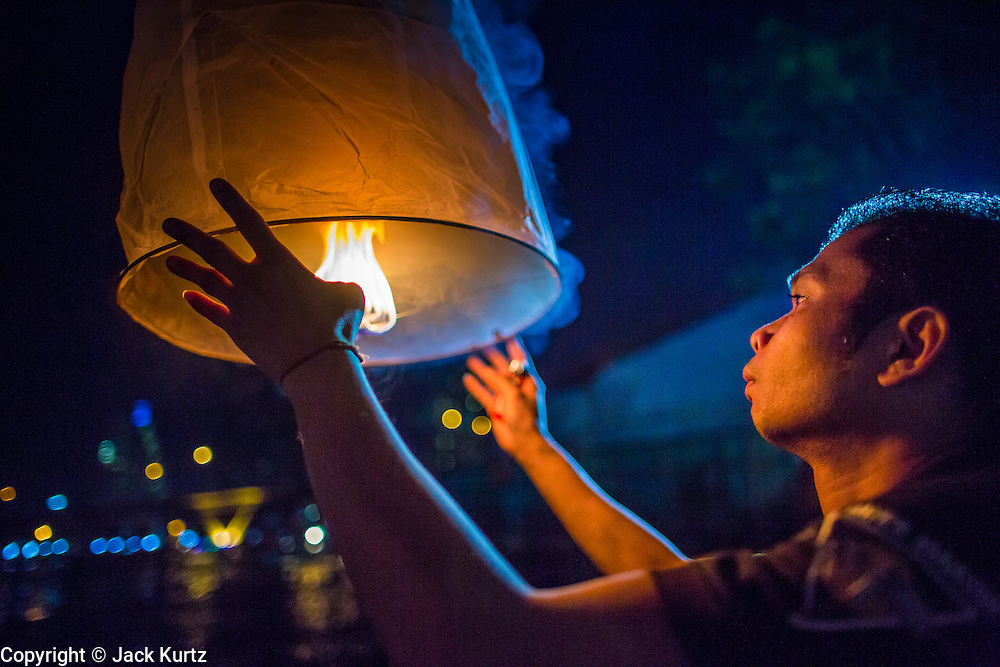 28 NOVEMBER 2012 - BANGKOK, THAILAND:  A man tries to light a Khom Loi lantern  during Loy Krathong at Wat Yannawa in Bangkok. The lanterns are a part of the Loy Krathong tradition in northern Thailand, and are becoming popular in Bangkok. But authorities don't allow their use in Bangkok because of the fire danger. They try to stop people from launching the lanterns in Bangkok. Loy Krathong takes place on the evening of the full moon of the 12th month in the traditional Thai lunar calendar. In the western calendar this usually falls in November. Loy means 'to float', while krathong refers to the usually lotus-shaped container which floats on the water. Traditional krathongs are made of the layers of the trunk of a banana tree or a spider lily plant. Now, many people use krathongs of baked bread which disintegrate in the water and feed the fish. A krathong is decorated with elaborately folded banana leaves, incense sticks, and a candle. A small coin is sometimes included as an offering to the river spirits. On the night of the full moon, Thais launch their krathong on a river, canal or a pond, making a wish as they do so.   PHOTO BY JACK KURTZ