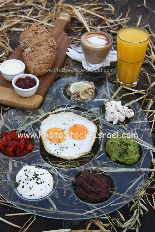 Traditional Israeli Breakfast with two fried eggs, cheeses, salads, fresh bread, orange juice and a cup of cappuccino
