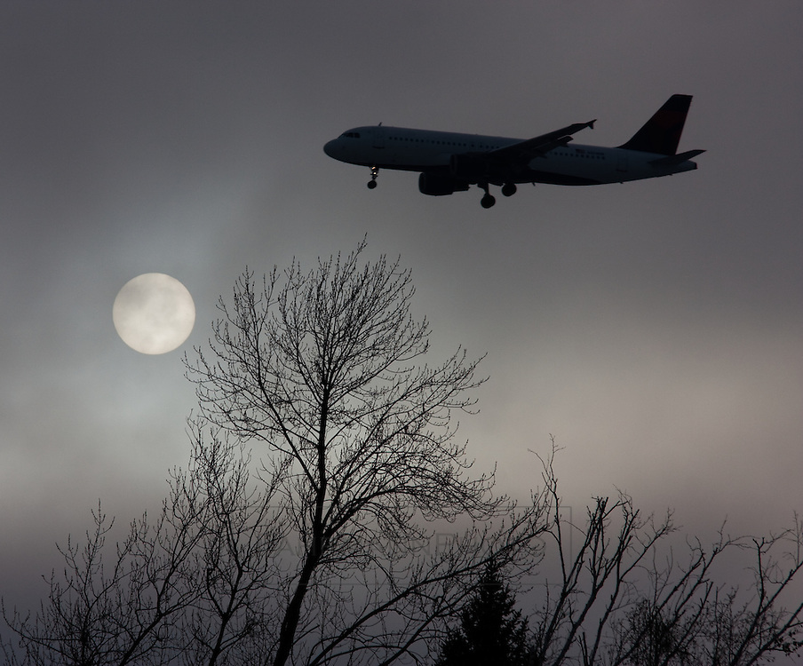 A commercial jet makes its approach for landing at the airport.  The Sun shines tentatively behind hazy clouds.