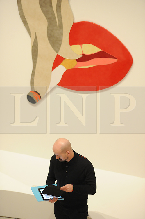 © Licensed to London News Pictures. 21/10/2013. London, UK. A man stands in front of Smoker Banner by Tom Wesselman at The Pop Art Design Exhibition preview at The Barbican Centre. Photo credit : David Mirzoeff/LNP