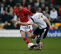 Wrexham's Matty Done (red) forces Marc Edworthy of Derby County (white) to back-pedal.