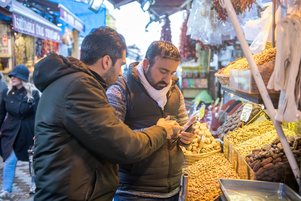 Two adult males point and look at cellphone together in front of market stall at outdoor marketplace, Istanbul, Turkey.