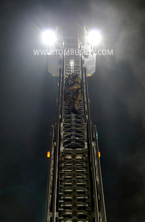 Middletown, New York - A firefighter climbs a ladder at the scene of a fire on Commonwealth Avenue on July 2, 2012. The fire started at about 3:30 a.m.