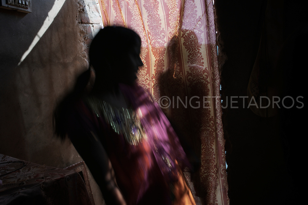 A young niece of the bride peeps through the curtains where the bride is readying herself.<br />