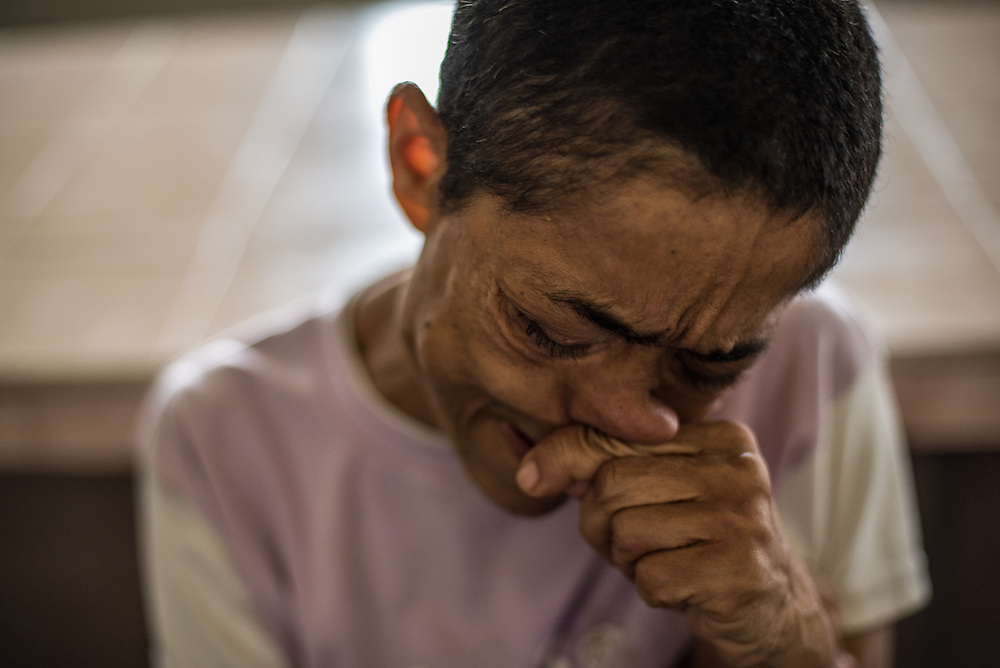 BARQUISIMETO, VENEZUELA - JULY 28, 2016: Schizophrenic patient, Levia Bracho cries because her body is painfully itchy because she is infected with scabies. Bracho is violent, yells at other patients and gets into fights when she does not have all of her medications.  The economic crisis that has left Venezuela with little hard currency has also severely affected its public health system, crippling hospitals like El Pampero Psychiatric Hospital by leaving it without the resources it needs to take care of patients living there, the majority of whom have been abandoned by their families and rely completely on the state to meet their basic needs, and who could live much more fulfilling lives if they had the medicines that they need. The hospital does not even have basic hygiene or cleaning supplies.  There is no soap, no shampoo, no tooth paste, no toilet paper.  Patients relieve themselves in the common areas and patio area, and clean themselves only with water. Nearly every patient is infected with scabies because they do not have the resources to bathe properly or to have their threadbare, misfitted clothes washed as often as needed. To make matters worse, the hospital only has running water a few hours a day.  PHOTO: Meridith Kohut