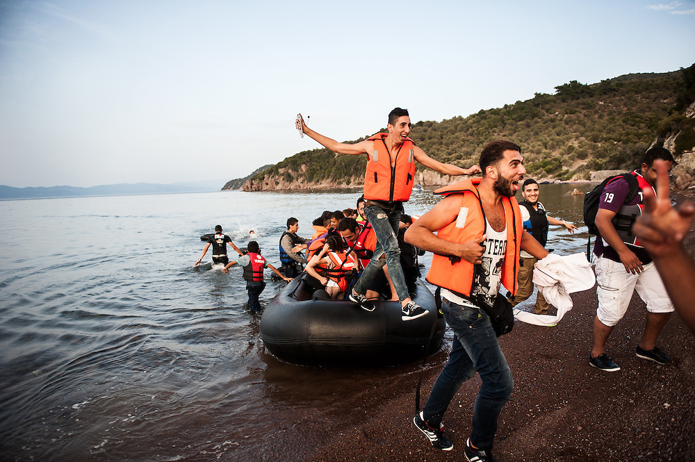 Syrians jumping off the dinghy that brought them to Greece and celebrate their safe arrival at a beach near Skala Sikamineas, Lesvos , Greece