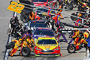 Joey Logano (22) and other racers make a pit stop during a NASCAR Cup Series auto race at Kansas Speedway in Kansas City, Kan., Sunday, Oct 21, 2018. (AP Photo/Colin E. Braley)