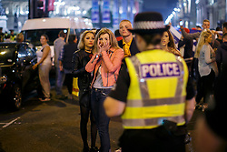 © Licensed to London News Pictures. 19/09/2014. Glasgow, UK. A group of young people on a night out caught in a police line whilst pro-unionists and Scottish independence supporters being separated at George Square in Glasgow as Scotland decides to stay in the union and First Minister Alex Salmond resigns over the results of the Scottish independence referendum on Friday, 19 September 2014. Photo credit : Tolga Akmen/LNP