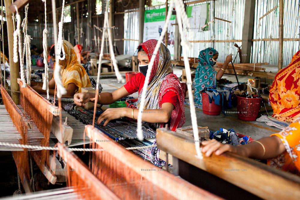(L-R) Mosiammat Rahimah Begum (yellow sari) and Mosammat Reshona Khatun (center, red sari) work on their rugs at the Mornia Kik Rug Factory in Doani Villlage, Haragach Upazila, Rangpur, Bangladesh on 19th September 2011 where they work alongside 25 rural village women making rugs for German textile discounter Kik. Over 400 women have been economically empowered through the CARE Bangladesh WONDER Project that was completed recently. The WONDER Project's goals were to create sustainable income and employment opportunities for extremely poor women by training them in rug production for export. The women now earn about 4000 Bangladeshi Taka per month. The WONDER Project has now moved into a new phase that focusses on general healthcare, workplace safety and nutritional training and awareness programs. Photo by Suzanne Lee for The Guardian