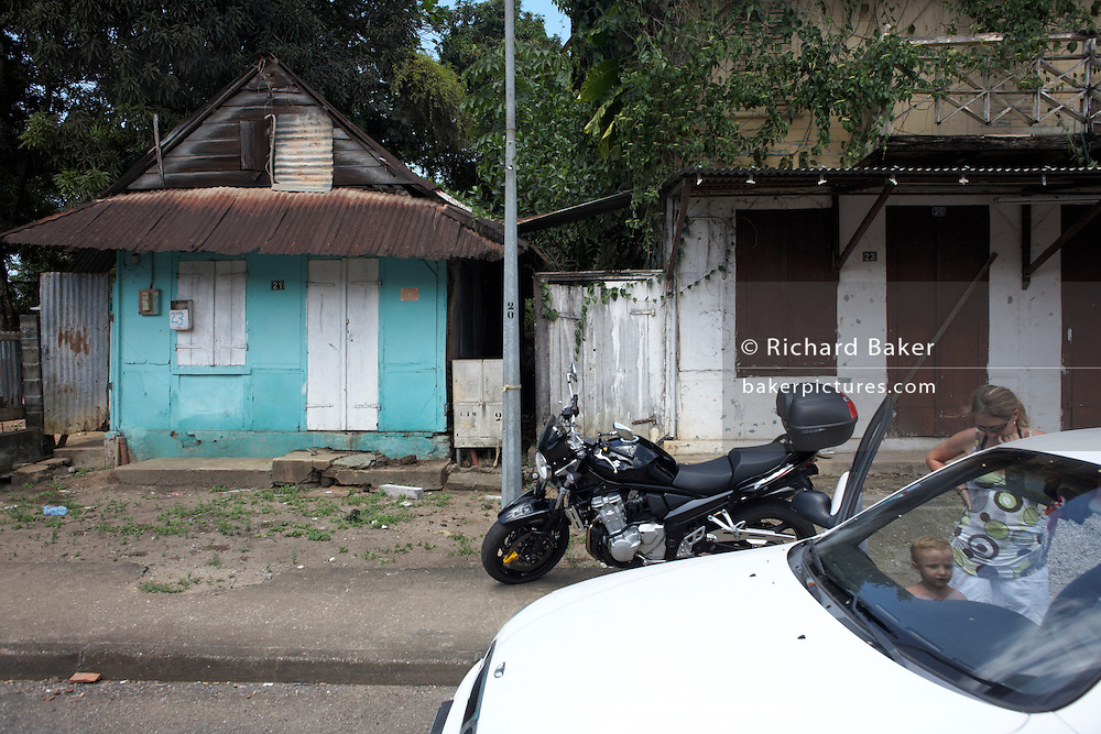 European mother and child board car near traditional ramshackle Creole house in town of Sinnamary, French Guiana.
