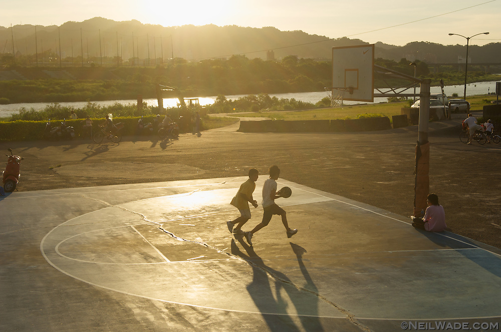 Two teens play basketball at sunset in Taipei, Taiwan.