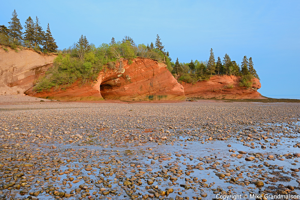 Sea caves in red cliffs along the Bay of Fundy<br /> St. Martins<br /> New Brunswick<br /> Canada