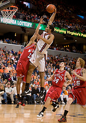 Virginia forward Mike Scott (32) goes up for a tomahawk dunk but is fouled by North Carolina State guard Marques Johnson (13).  The Virginia Cavaliers men's basketball team defeated the North Carolina State Wolfpack 78-60 at the John Paul Jones Arena in Charlottesville, VA on February 24, 2008.