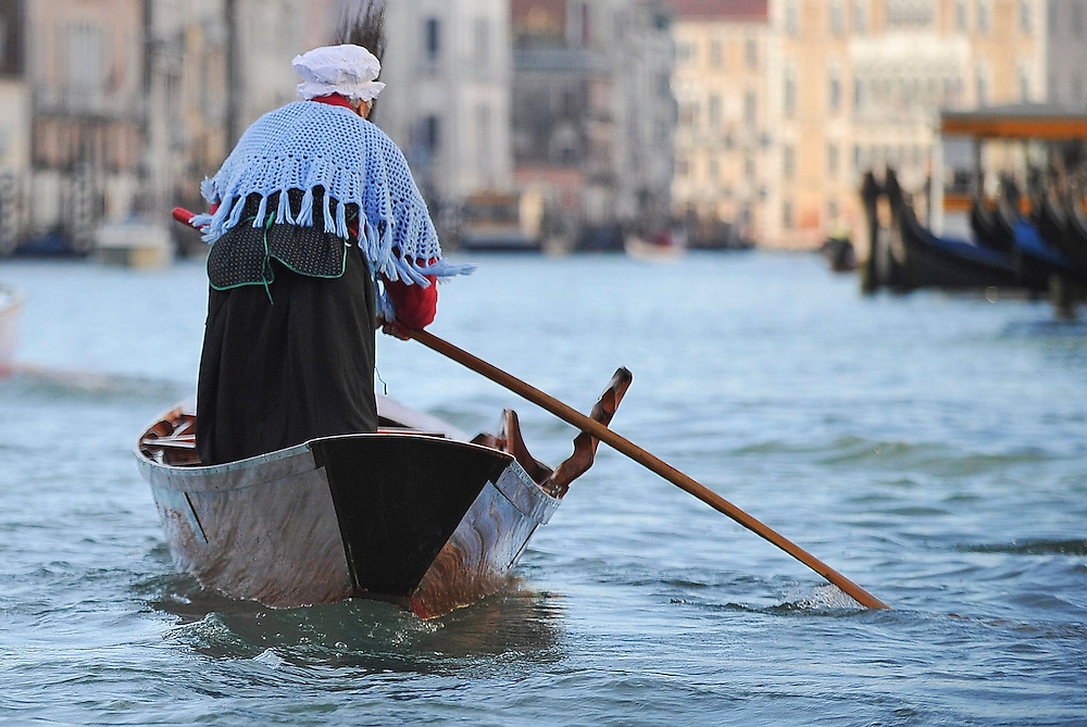 "VENICE, ITALY - JANUARY 06:  One of the rowers dressed in costume heads towards the start line few minutes ahead of the ""Befana"" Regatta on January 6, 2014 in Venice, Italy. In Italian folklore, Befana is an old woman who delivers gifts to children throughout Italy on the feast of the Epiphany on January 6 in a similar way to Saint Nicholas or Santa Claus.  (Photo by Marco Secchi/Getty Images)"