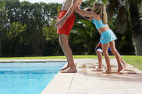 Children (5-6) pushing father into swimming pool