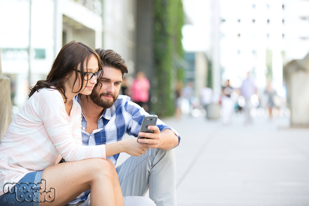 Couple using smart phone together while sitting on steps in city