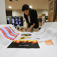 Jim Hill High School student Lalah Sadiqulden, 14, of Jackson puts a few last minute items in place on her board for Friday's State Science Fair held at Northeast Community College in Booneville.