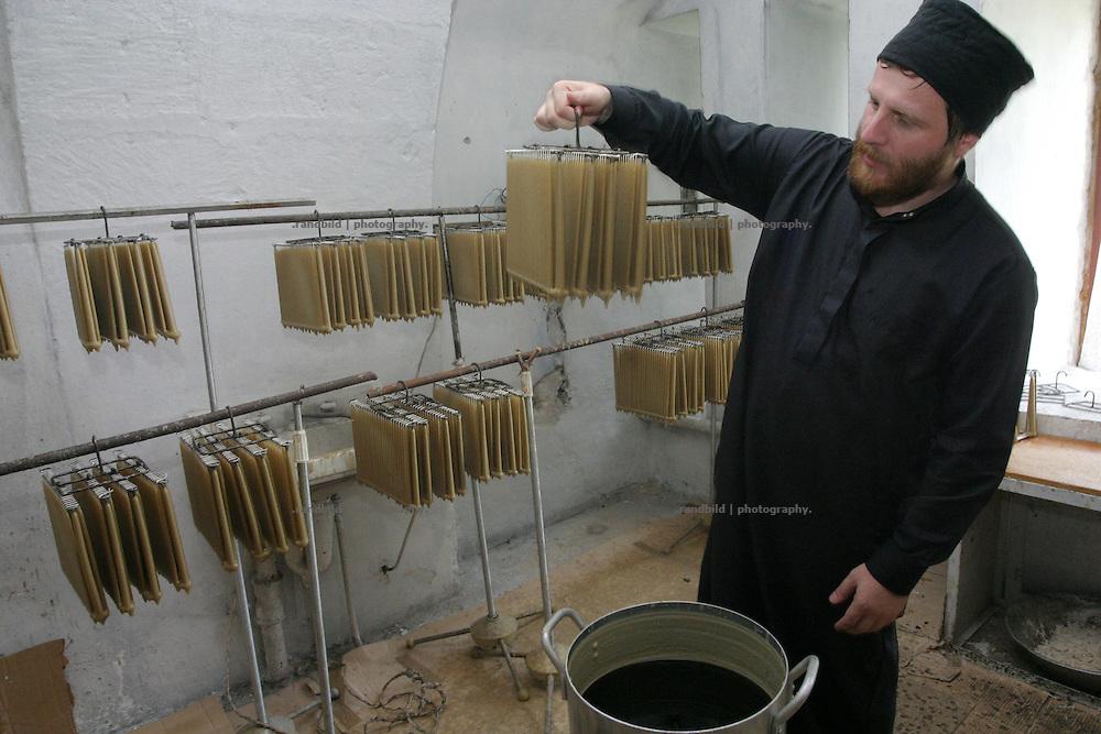 Georgien/Abchasien, Nowy Afon, 2006-08-27, Ein orthodoxer Priester zeigt die Kerzenproduktion des Klosters Nowy Afon. Abchasien erklärte sich 1992 unabhängig von Georgien. Nach einem einjährigen blutigen Krieg zwischen den Abchasen und Georgiern besteht seit 1994 ein brüchiger Waffenstillstand, der von einer UNO-Beobachtermission unter personeller Beteiligung Deutschlands überwacht wird. Trotzdem gibt es, vor allem im Kodorital immer wieder bewaffnete Auseinandersetzungen zwischen den Armee der Länder sowie irregulären Kämpfern.  (An orthodox priest shows the candle production of the monastery of Nowy Afon. Abkhazia declared itself independent from Georgia in 1992. After a bloody civil war a UNO mission observing the ceasefire line between Georgia and Abkhazia since 1994. Nevertheless nearly every day armed incidents take place in the Kodori gorge between the both armys and unregular fighters )