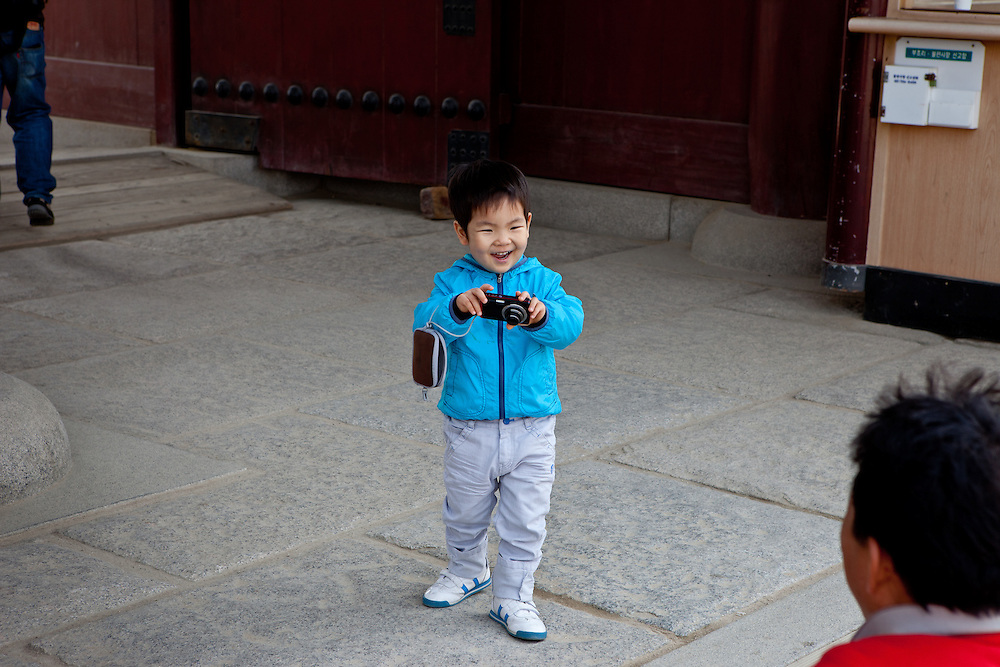 Child taking a photograph of her father at the at Gwanghwamun of Gyeongbokgung Palace, the main royal palace of Joseon Dynasty, the spectacle is based on the formality from the early 15th century.