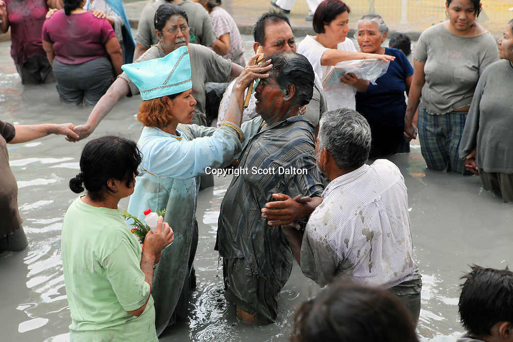 A faith healer conducts a ceremony on a follower at a mud bath that is believed to have healing properties in Espinazo, Mexico on October 16, 2009. Followers of Nino Fidencio believe that his spirit can posses other healers, who once possessed speak in a child like voice and perform a variety of medical cures on their followers. His believers, an estimated 20,000, gather in his hometown for a three-day festival twice a year in March and October. (Photo/Scott Dalton).