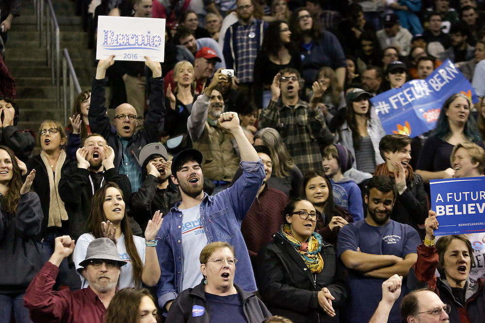 People cheer at a rally for Democratic presidential candidate Bernie Sanders at Key Arena on March 20, 2016 in Seattle.  AFP PHOTO/JASON REDMOND