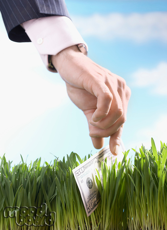 Businessman picking up fifty-dollar bill from grass close-up of hand
