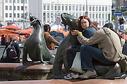 Kauppatori (Market Square). Young couple with bronze seals on a fountain.