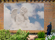 Photoshop composition, angel in clouds artwork, on a brick wall of an old building, with the artist looking at the result.