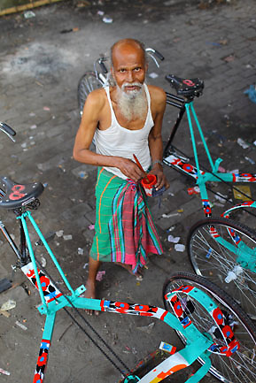 Rickshaw painter (Old Dhaka, Bangladesh). The rickshaw painters are the most considered workers in the local rickshaw industry in Bangladesh. They can be freelance, working for several rickshaw workshops, or even working at home... They have a biggest salary and autonomy related to the other workers.  There are two kinds of painters for rickshaws: the ones drawing abstract patterns or small drawings on the rickshaw body and external elements, and the most prestigious ones are the ones drawing faces, people, landscapes, famous sights or events, etc. on the large metal sheet in the back of the rickshaw, and on the seat in front. These rickshaw painters are the ones signing their drawings.