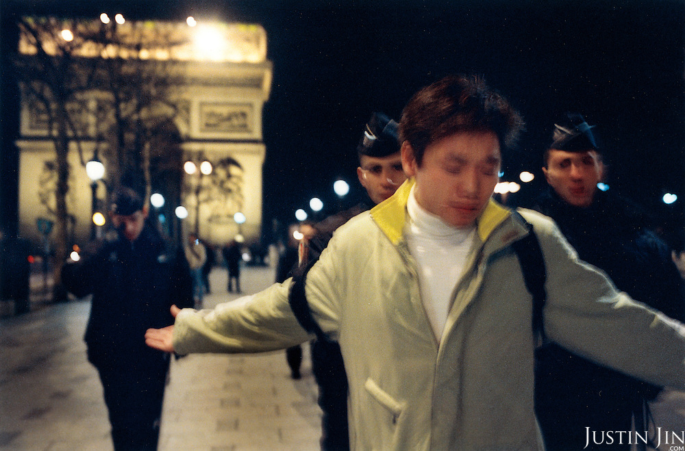 France, Paris, 05-2003..An illegal Chinese encounters police check in front of the Arc de Triumphe in Paris. They let him go and told him not to return to the area.