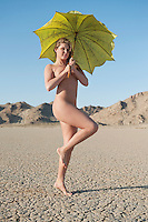 Full length of a young naked woman holding umbrella on barren landscape