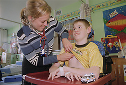 Female doctor using stethoscope to examine young boy with Cerebral Palsy who is sitting in wheelchair on Children's ward of hospital,