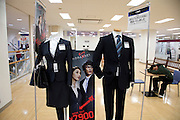 Japanese clothing store selling male and female black business suites with man sleeping in the background