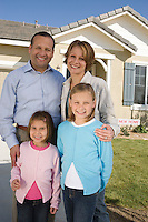 Portrait of family with two children (6-9) in front of new house