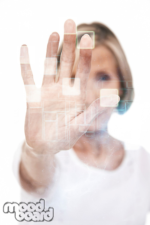 Closeup of a senior woman holding out palm of hand against white background