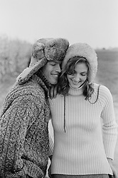 Couple in sweaters and fur hats outdoors