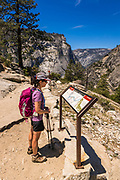 Hiker reading interpretive sign on the John Muir Trail, Yosemite National Park, California USA