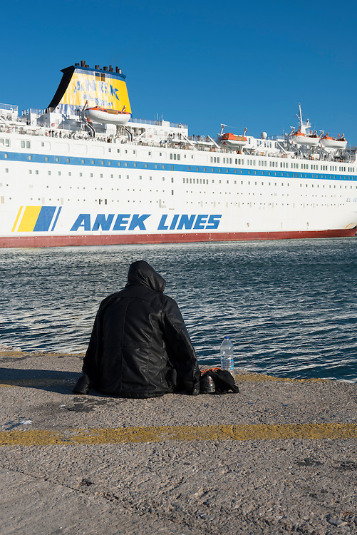 A 23-year-old migrant traveling from Kunduz, Afghanistan to the European mainland sits in the port of Mytilene on the Greek island of Lesbos