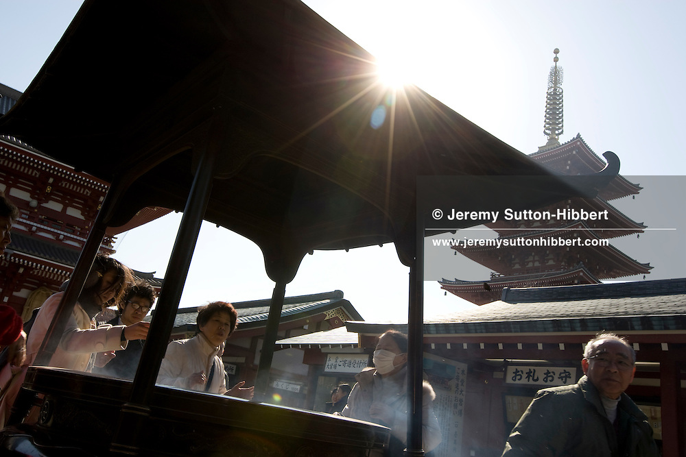 Visitors to Senso-ji temple wave incense smoke over themselves from an urn to ward off poor health, and to fix and cure ailments, in the Asakusa district, Tokyo, Japan, Monday 3rd March 2009.