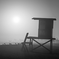 Newport Beach CA lifeguard tower M at sunset black and white photo. Newport Beach is a coastal city along the Pacific Ocean in Orange County Southern California in the Western United States of America. Copyright ⓒ 2017 Paul Velgos with all rights reserved.