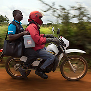 Data clerk Oscar Kai (blue shirt), prepares to head to an outreach clinic on a motorcycle , with his laptop and shoulder carried cooler of vaccines. After a 20 minute ride, a distance that would take a mother carrying her baby on foot, more than two hours, Mr. Kai sets up his laptop on a desk in a rural classroom where children will receive vaccinations, and their health records will be captured digitally.<br /> <br /> &quot;Because the database is digitized, it means its far easier to keep our records fresh, even if children move and access health services in different locations,&quot; says Dr.Benjamin Tsofa, the Kenyan health ministry's chief liaison on the study. <br /> <br /> In January 2011, the Kenyan government with support from the GAVI Alliance, introduced a new vaccine, PCV-10, which targets 10 bacteria than can cause Invasive Pneumococcal Disease.The vaccine's impact is monitored through an electronic database, part of the GAVI funded PCV impact study, which maps the growing coverage of the new vaccine. Already, here in Kilifi, the incidence of the illness in children aged five has gone down by approximately two-thirds.