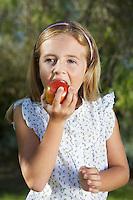 Portrait of girl (5-6) eating apple