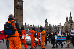London, February 14th 2015. Dozens of orange boiler-suit clad protesters march from Parliament Square to Downing Street in protest against the ongoing detention in Guantanamo Bay of British subject Shaker Amer, who has been held without charge for 13 years. PICTURED: Protesters march from Parliament Square to Richmond Terrace on Whitehall.