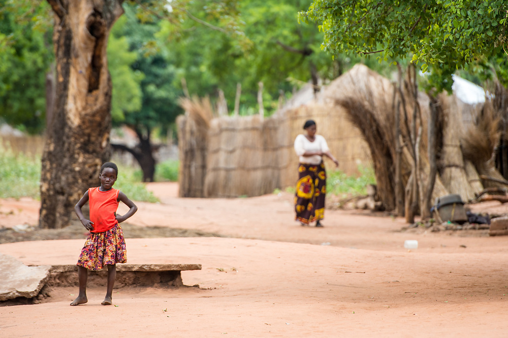 Young Zambian girl stops and poses with her hands on her hips in middle of village, Mukuni Village, Zambia