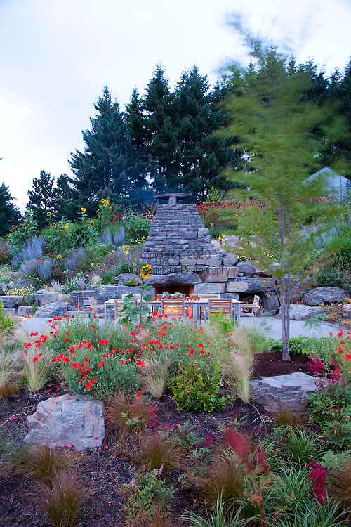 The evening view of the outdoor fireplace, dining area and surrounding landscaping.