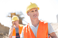 Male worker at construction site with colleague standing in background
