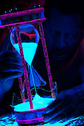 A screaming manholds a broken hourglass as sands spills onto a table.Black light