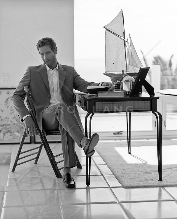 good looking man in a suit sitting at a desk at home
