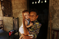A Colombian woman holds her grand-daughter at a house they rent near the border.  There are about 2000 people seeking refugee status in Venezuela, most of whom are Colombians who have fled their country due to increasing violence caused by the conflict in Colombia.  Unable to return to Colombia for fear for their lives, and unable to obtain legal refugee status in Venezuela, many Colombian families live along the border.