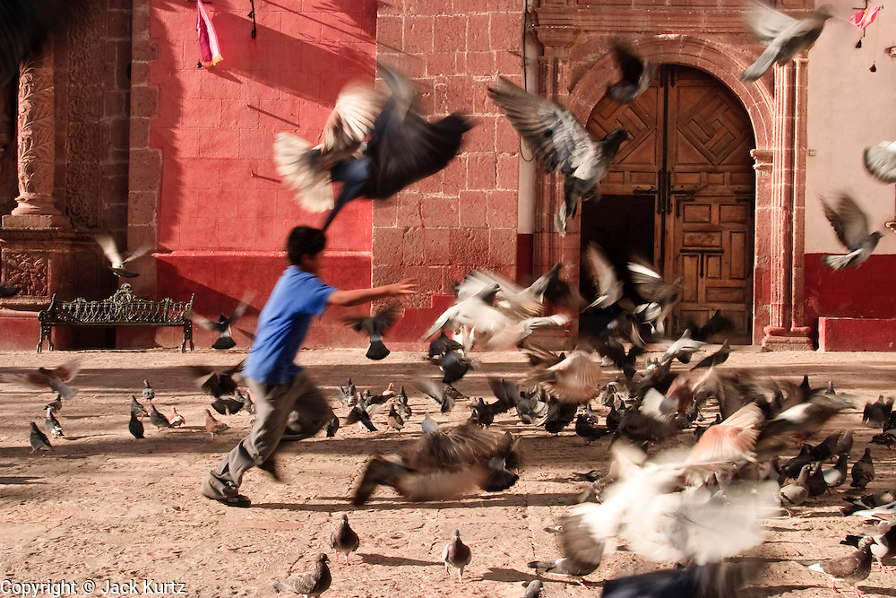 A boy chases pigeons in front of a Catholic church in San Miguel de Allende, Mexico. PHOTO BY JACK KURTZ